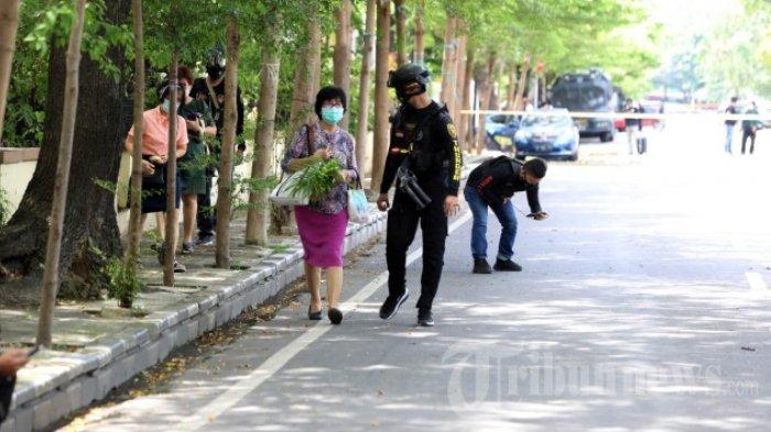 Jemaat berjalan keluar Gereja dan diamankan oleh petugas Kepolisian di Gereja Hati Yesus Yang Mahakudus atau Katedral Makassar, Minggu (28/3/2021). Polisi menyatakan bom yang meledak tersebut merupakan bom bunuh diri.