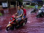 pengendara-motor-melintas-di-jalan-perkampungan-yang-tergenang-banjir-berwarna-merah-di-pekalongan.jpg