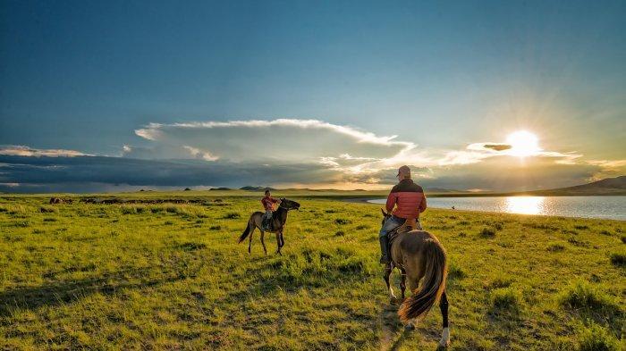 Anak-anak yang sedang menunggang kuda sembari menikmati sunset di Mongolia