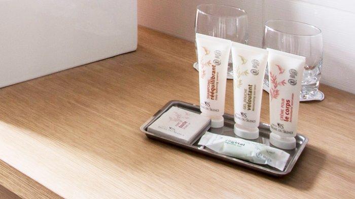 ILUSTRASI botol perlengkapan mandi dalam ukuran mini yang disediakan di kamar mandi hotel.