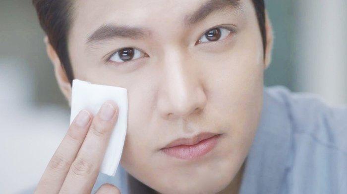 Ilustrasi seorang cowok yang tengah membersihkan wajah dengan kapas