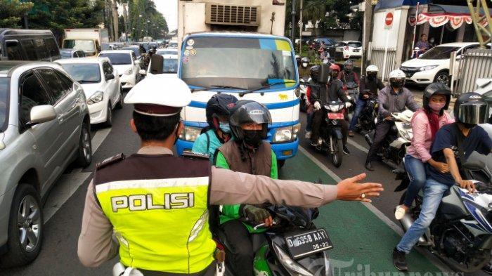 Petugas Kepolisian bersama Dinas Perhubungan (Dishub) Kota Bandung melakukan uji coba pemberlakuan ganjil genap kendaraan bermotor pribadi di persimpangan Jalan Tamblong-Jalan Asia Afrika, Kota Bandung, Jawa Barat,