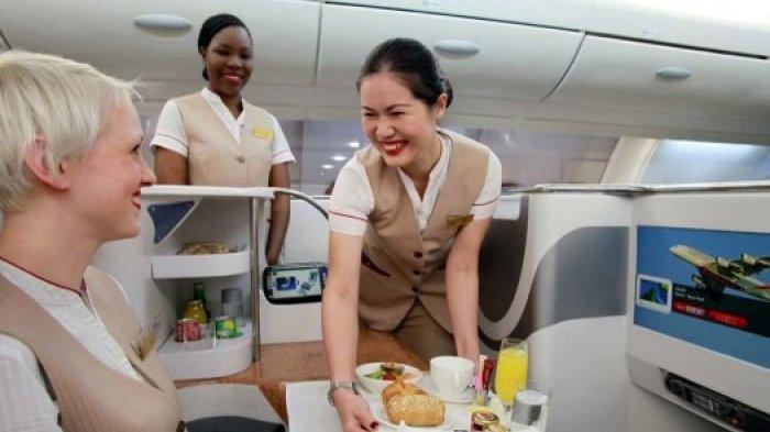 Seorang pramugari Emirates sedang melayani penumpang kelas bisnis