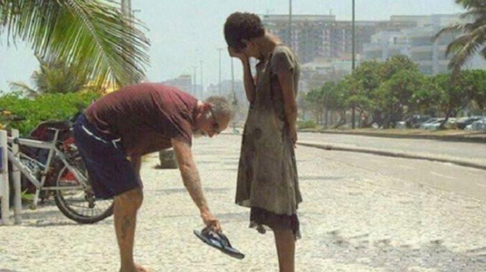 Pria ini menwarkan alas kakinya pada seorang gadis di Rio de Janeiro, Brasil.