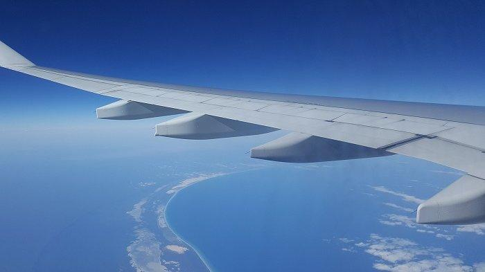 Ilustrasi pesawat yang sedang melintasi lautan.