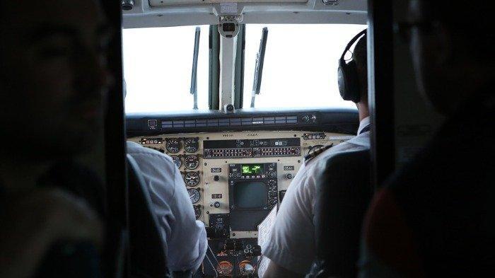 Ilustrasi pilot duduk di ruangan kokpit pesawat