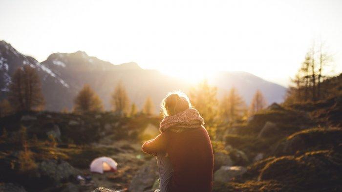 Ilustrasi seorang wanita menikmati sunset di tempat camping