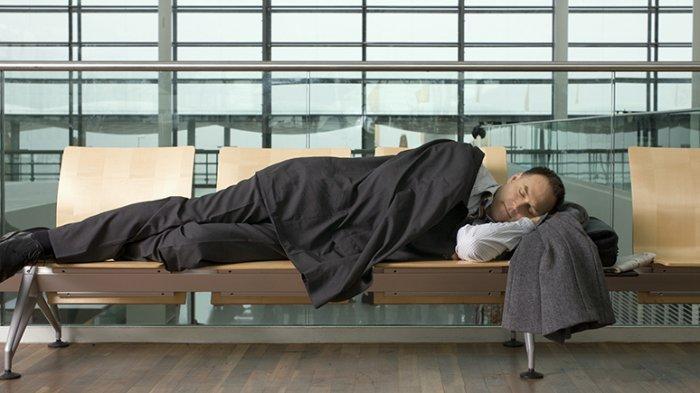 Ilustrasi - seorang pria tidur di bandara
