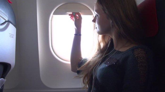 Ilustrasi penumpang duduk di dekat jendela pesawat