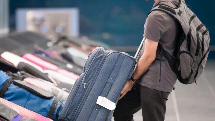 Ilustrasi - Penumpang yang mengambil koper.