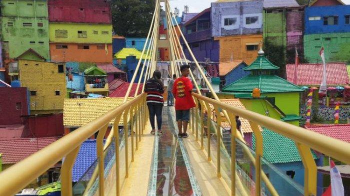 Sejumlah wisatawan saat melintas di jembatan kaca yang menghubungkan Kampung Warna - warni dan Kampung Tridi di Kota Malang, Jawa Timur, Selasa (10/10/2017).