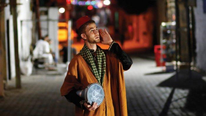 Seorang mesaharati membangunkan orang untuk sahur saat bulan Ramadan.
