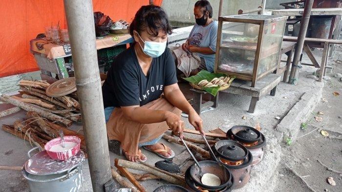 Murtini sedang membuat serabi kocor, bersama sang kakak, Ngadinem, di belakangnya
