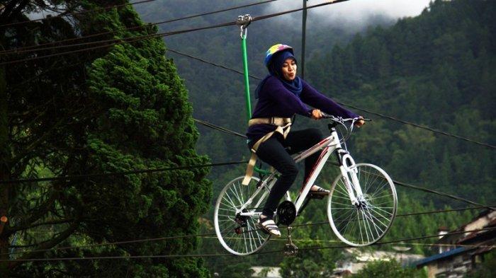 Seorang pengunjung naik sepeda gantung the geong di objek wisata Guci Kabupaten Tegal.