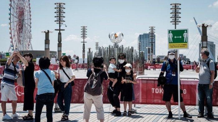 Orang-orang berfoto di dekat api Olimpiade yang menyala di kuali di Jembatan Ariake Yume-no-Ohashi di Tokyo pada 25 Juli 2021.
