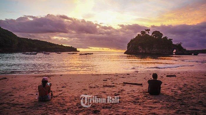 Dua orang wisatawan tampak menikmati keindahan Pantai Crystal Bay di Desa Sakti, Nusa Penida, Bali, Minggu (21/4/2019).