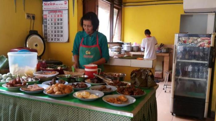 Ibu Yayuk, seorang pegawai Depot Nasi Pecel 99 milik Karyono di Jalan Cokroaminoto No 99, Kota Madiun, Jawa Timur, sedang melayani pelanggannya.