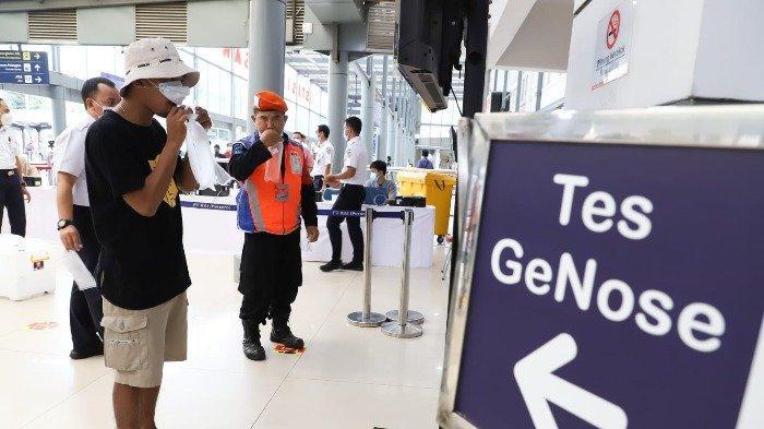 Seorang pelanggan kereta api jarak jauh sedang melakukan pemriksaan GeNose C19 di stasiun.