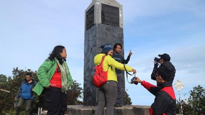 Pendaki berfoto di Puncak Hargo Dumilah Gunung Lawu, Jawa Timur, Jumat (29/12/2017). Sejumlah pendaki memanfaatkan momen libur akhir tahun untuk mendaki Gunung Lawu.