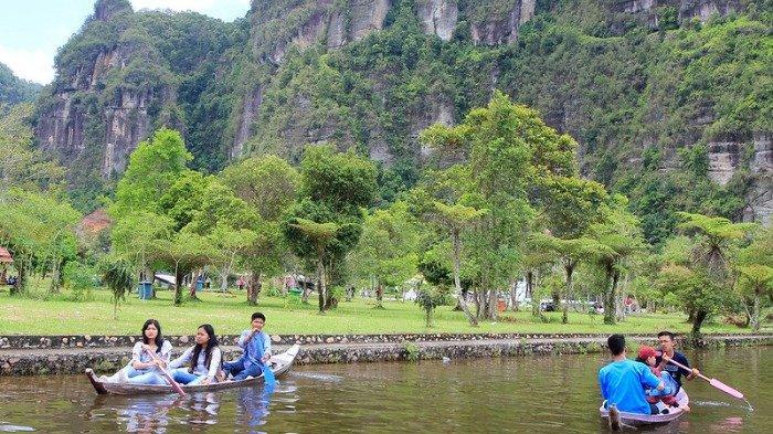 Pengunjung menikmati salah satu wahana permainan (bermain perahu) di Lembah Harau, Kabupaten Lima Puluh Kota, Sumatera Barat
