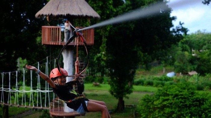 Pengunjung nyobain wahana flying fox di Manado Treetop Zipline Park