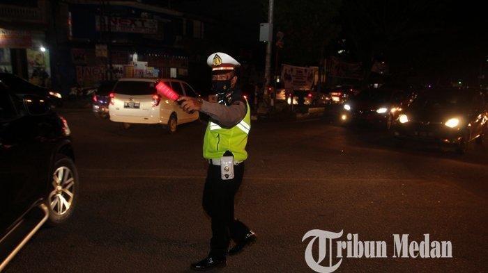 Petugas Kepolisian Satlantas terlihat mengatur arus lalu lintas di titik penyekatan pusat kota di Pertigaan Simpang USU, Medan, Sabtu (10/7/2021). Hari ini mulai berlaku PPKM Darurat di Kota Medan.