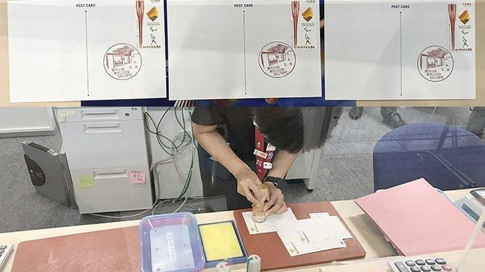 Petugas pos dari Kantor Pos Big Sight Tokyo sedang memberikan cap khusus pada tiga macam kartu pos yang diberikan gratis oleh kantor pos di Jepang dalam rangka Olimpiade Tokyo 2020.