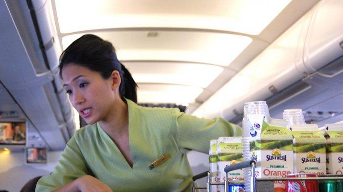 Pramugari yang sedang melayani penumpang pesawat