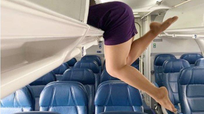Ilustrasi seorang pramugari berpose di tempat bagasi kabin pesawat.