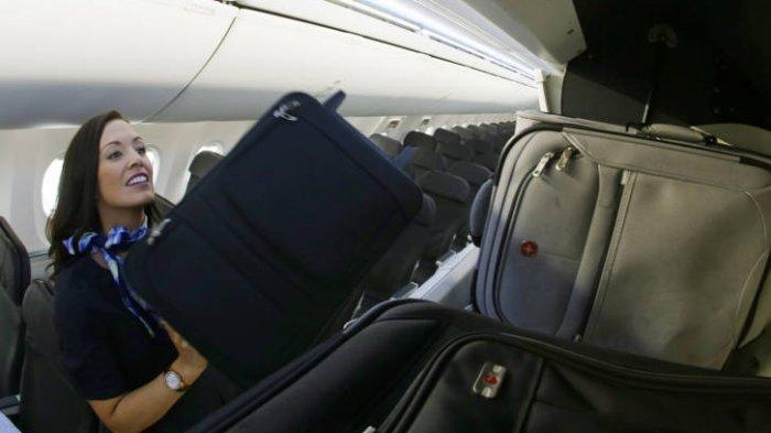 Pramugari membantu penumpang memasukkan barang ke bagasi.