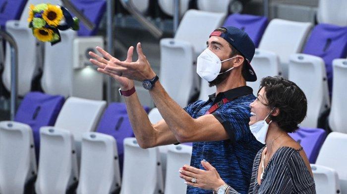 Reaksi mantan perenang AS Michael Phelps saat ia menangkap karangan bunga saat menonton upacara medali untuk nomor 4x200m gaya bebas estafet renang putri selama Olimpiade Tokyo 2020 di Tokyo Aquatics Center di Tokyo pada 29 Juli 2021.