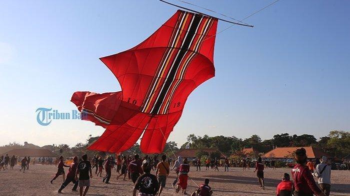 LAYANGAN RAKSASA - Sejumlah warga binaan Lapas Kerobokan menerbangkan layang-layang jenis Bebean raksasa pada lomba layang-layang Denpasar Kite Festival 2019 di Pantai Mertasari, Denpasar, Minggu (28/7/2019).