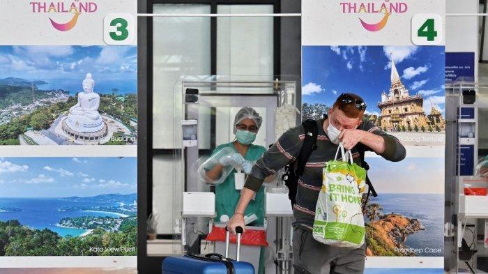 Dalam file foto ini diambil pada 1 Juli 2021 seorang penumpang internasional bereaksi setelah seorang pekerja medis memberinya tes swab Covid-19 setelah kedatangan mereka untuk skema pariwisata