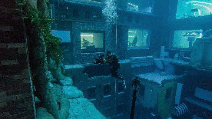 Seorang penyelam menangkap gambar kota tiruan di Deep Dive Dubai, kolam renang terdalam di dunia mencapai 60m, di Uni Emirat Arab, pada 10 Juli 2021. Kota superlatif, dengan menara tertinggi di dunia di antara banyak rekornya , Dubai kini memiliki kolam renang terdalam di planet ini lengkap dengan