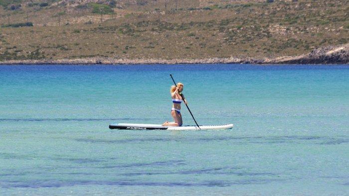 Seorang wanita melakukan paddleboarding menggunakan papan dayung