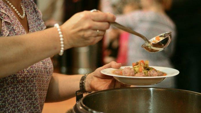 Seorang wanita yang sedang menyajikan sup