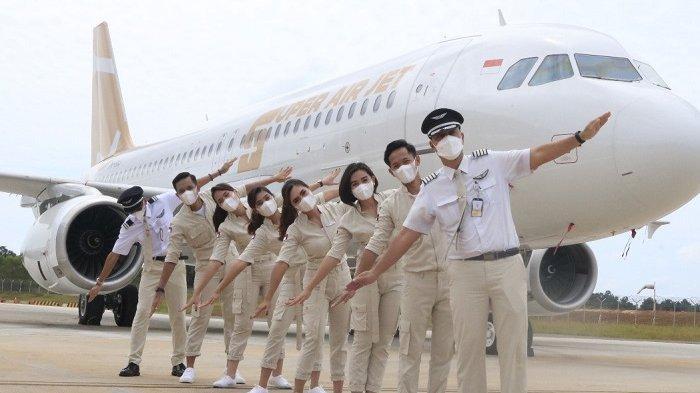 Para pramugari Super Air Jet memakai sneakers berwarna putih dan tas selempang ketika bertugas melayani penumpang.