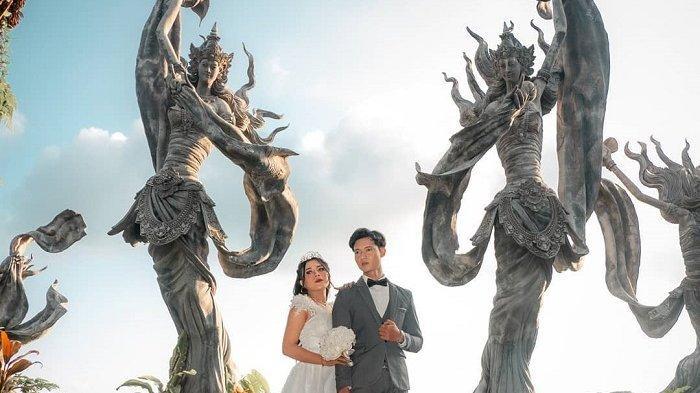 Bak negeri dongeng, pasangan ini berfoto dengan latar belakang patung bidadari di Taman Dedari