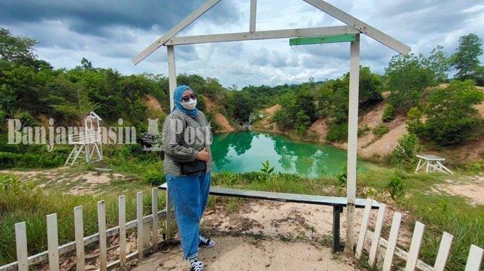 Pengunjung difoto dengan latar Danau Biru di Kelurahan Sungai Tiung, Kecamatan Cempaka, Kota Banjarbaru, Kalimantan Selatan, Minggu (22/8/2021).
