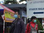 dua-orang-menggunakan-masker-di-depan-stasiun-malang.jpg