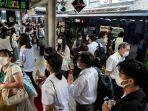 orang-orang-berjalan-di-peron-stasiun-kereta-api-di-tokyo-pada-28-juli-2021.jpg