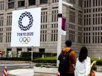 orang-orang-menyeberang-jalan-di-dekat-logo-olimpiade-tokyo-2020-di-tokyo-pada-15-juli-2021.jpg