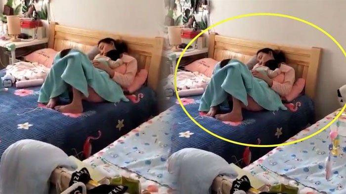 Seorang istri tidur sambil gendong anaknya