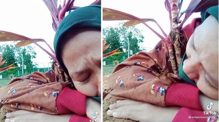 Seorang wanita menangis di depan makam sang ibunda
