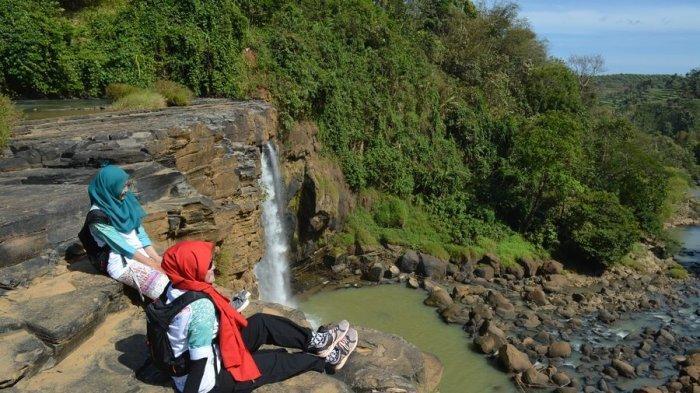 Pengunjung menikmati pemandangan dari puncak Curug Awang di Geopark Ciletuh, Kabupaten Sukabumi