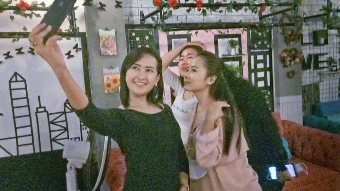 Astri dan kawannya sedang berswafoto di kedai Kopi Kabut Mican,  Pasirkareumbi, Kabupaten Subang.