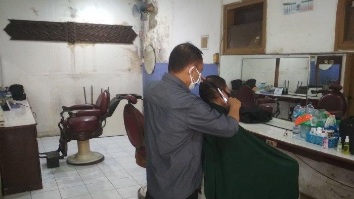 Barberman sedang mencukur rambut pelanggan di Pangkas Rambut Sawargi yang berlokasi Jl. Saad No.16, Kb Pisang, Kec. Sumur Bandung, Kota Bandung