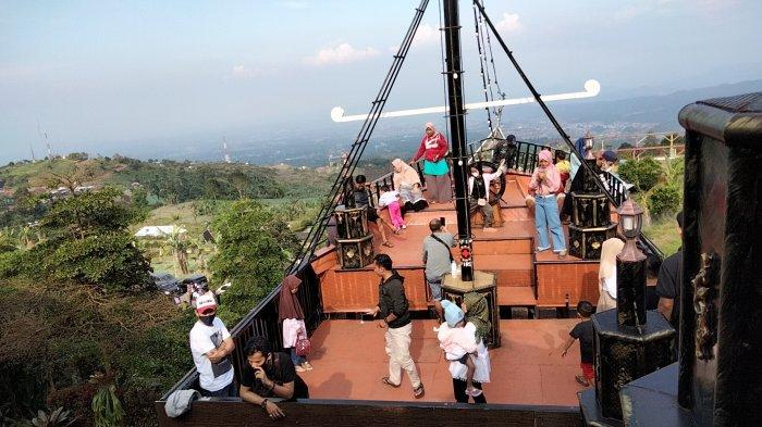 Wisatawan melihat pemandangan dari perahu besar di Pondok Cai Pinus, Desa Cisantana, Kecamatan Cigugur, Kuningan