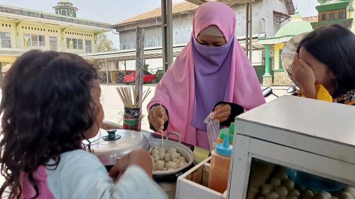 Casinta saat melayani anak-anak yang membeli cilok di Desa Sumuradem Timur, Kecamatan Sukra, Kabupaten Indramayu,