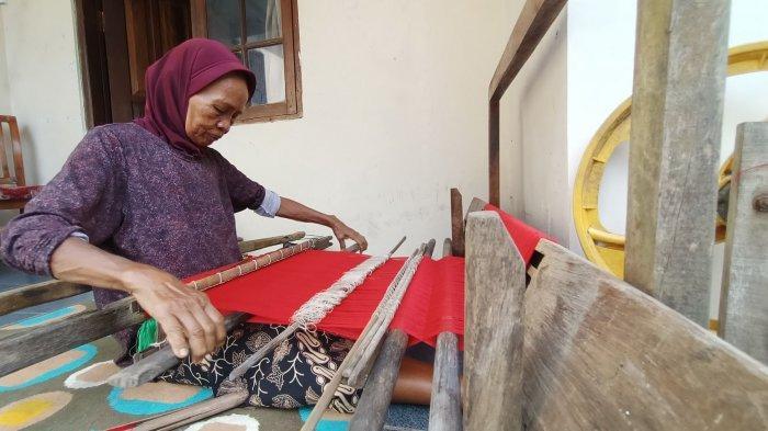KAIN GEDOGAN - Sunarih (62) saat menenun kain gedogan di kediamannya di Desa Juntikebon, Kecamatan Juntinyuat, Kabupaten Indramayu, Minggu (21/3/2021).
